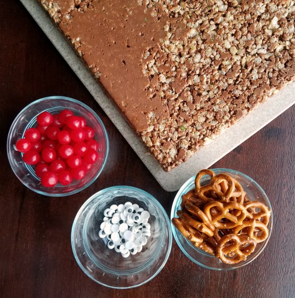 chocolate peanut butter rice krispies with bowls of pretzels, eyes and sour cherry candy.