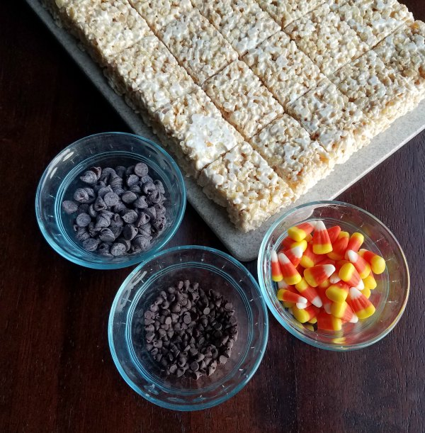 white rice krispie treats with bowls of mini chocolate chips, chocolate chips and candy corn.