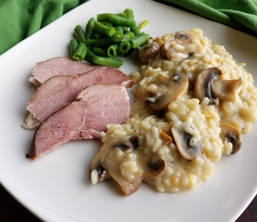 plate with mushroom risotto, green beans and slices of ham