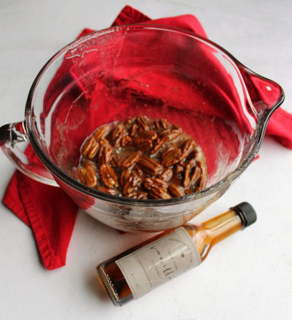 glass bowl filled with sugar syrup and pecans with bottle of homemade vanilla extract.