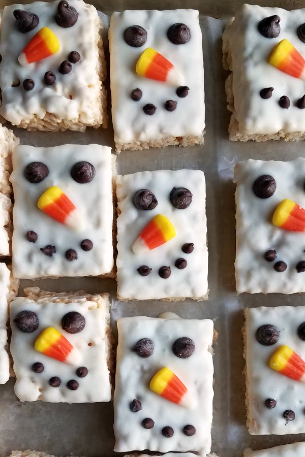 Tray of white chocolate dipped snowman rice krispie treats.