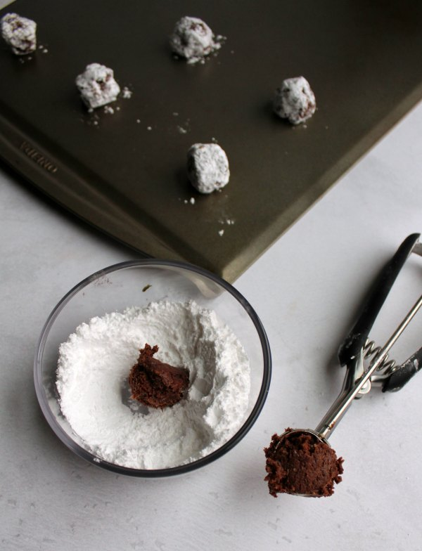 small cookie scoop putting balls of dough into bowl of powdered sugar and onto cookie sheet pan