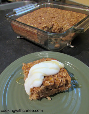 Thick and soft square of banana baked oatmeal topped with vanilla yogurt. Remaining pan of oatmeal in background