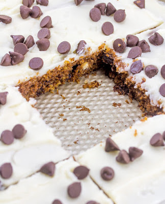 sheet pan filled with white icing topped chocolate chip Texas sheet cake with square piece missing