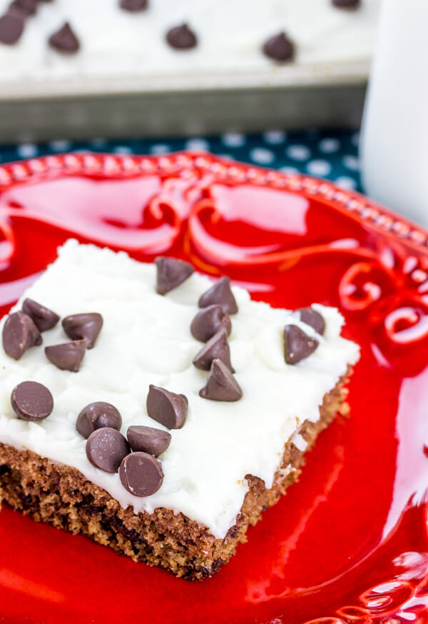 piece of cookie dough sheet cake with smooth white icing and chocolate chips on top