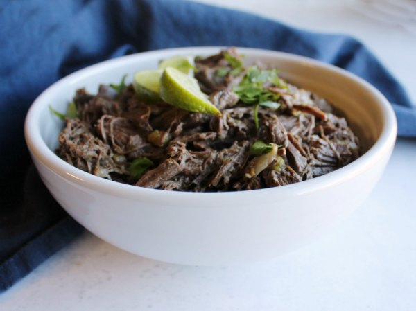 serving bowl of shredded barbacoa style venison topped with lime wedges and cilantro