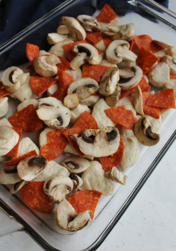 biscuits with pepperoni and mushrooms in pan ready to turn into pizza casserole bake.