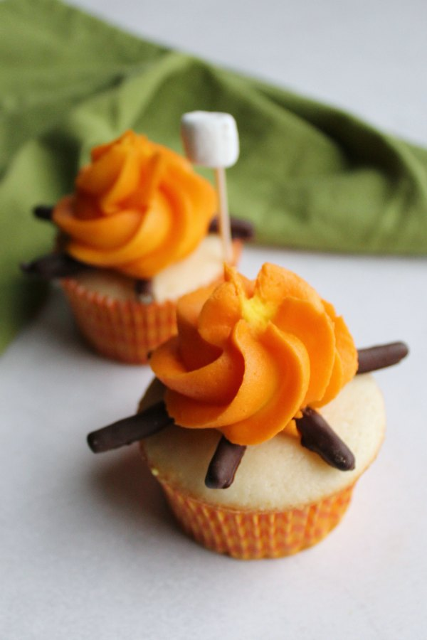 two campfire cupcakes with a mini marshmallow on a stick ready to be roasted