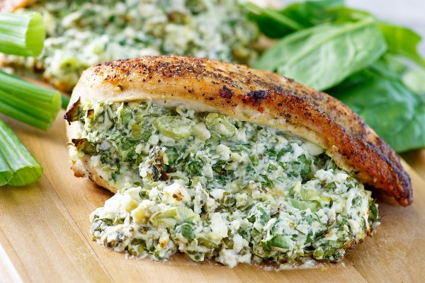 close up of a chicken breast stuffed with creamy feta, spinach and green onion filling