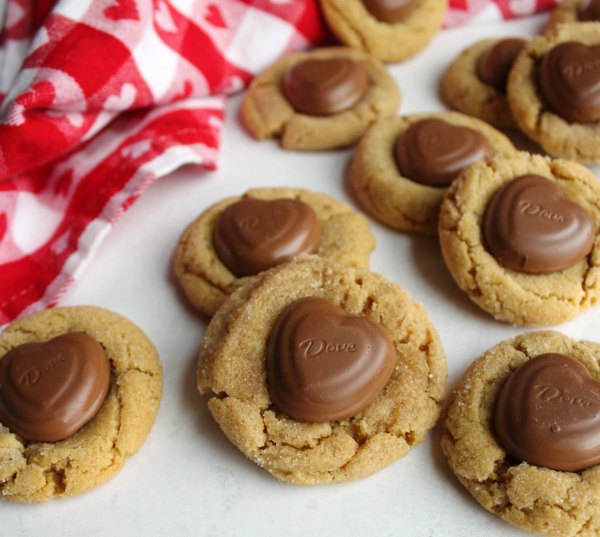 pile of peanut butter blossom cookies with chocolate heart centers.
