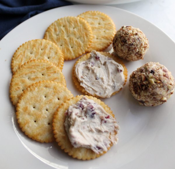plate with 2 mini cranberry cheese balls, butter crackers and some cheese ball spread on crackers