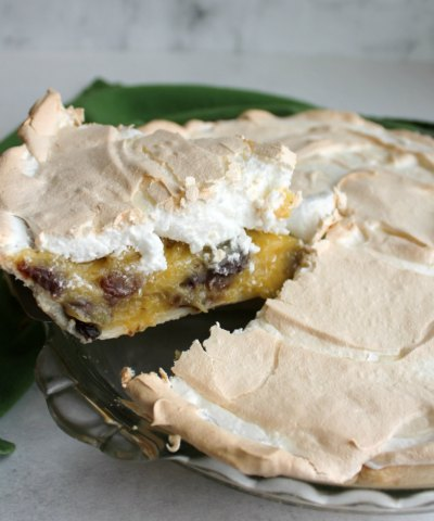 first slice of meringue topped sour cream and raisin pie being lifted out of the pan.