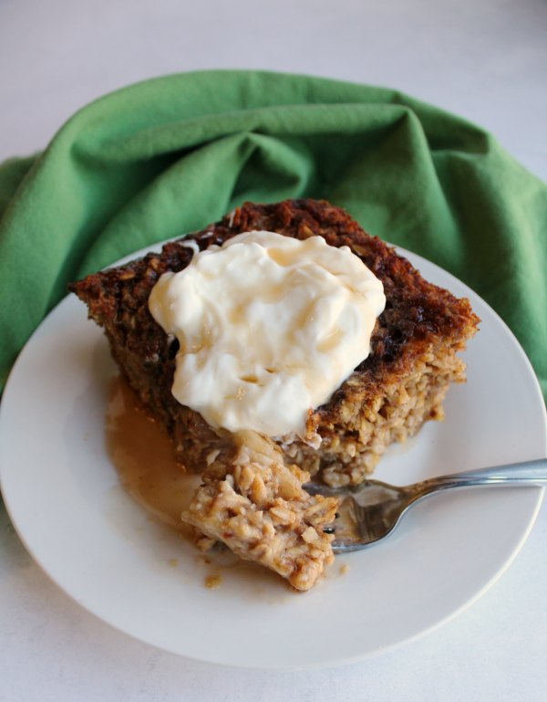 fork of cinnamon banana bread baked oatmeal in front of piece topped with honey and yogurt.