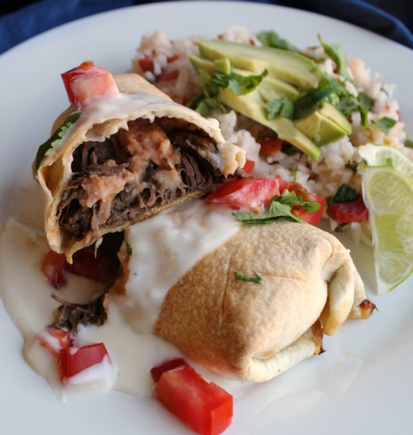 close up of baked chimichanga cut in half with shredded meat and refried beans showing