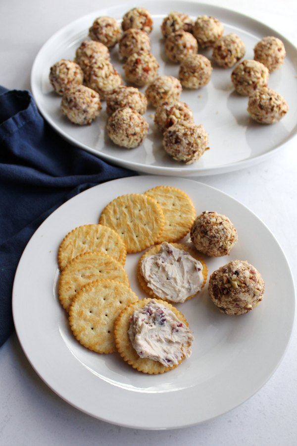 small plate of mini cranberry cheese balls and crackers on plate with platter of cheese balls in background