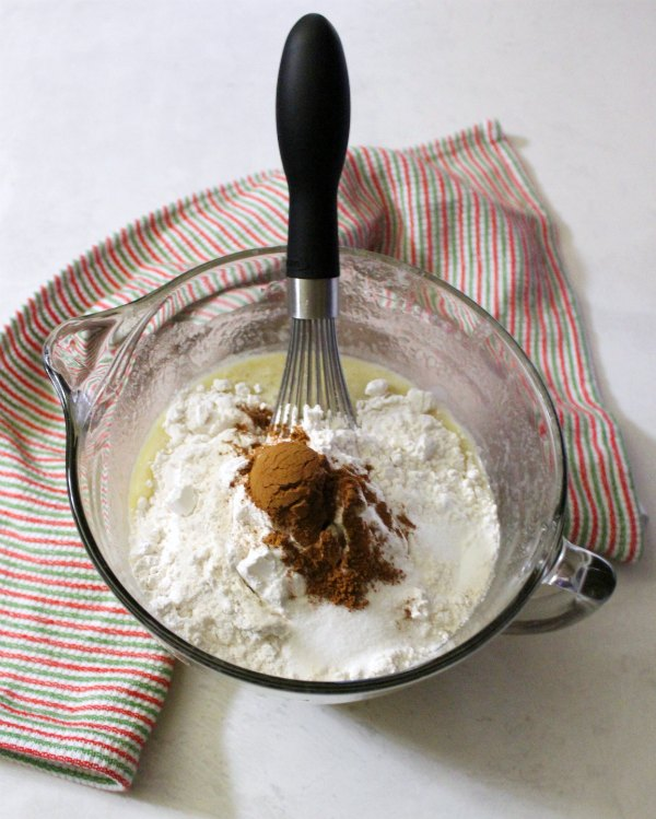 Banana bread ingredients in bowl with whisk.