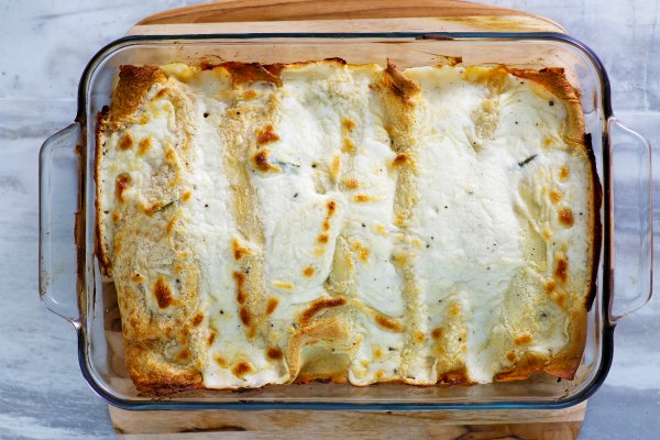 pan of creamy chicken and mushroom stuffed baked crepes in pan fresh from oven.