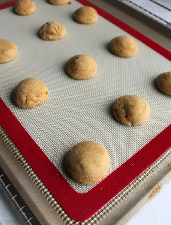 warm peanut butter cookies on baking tray, fresh from the oven and waiting for their chocolate centers