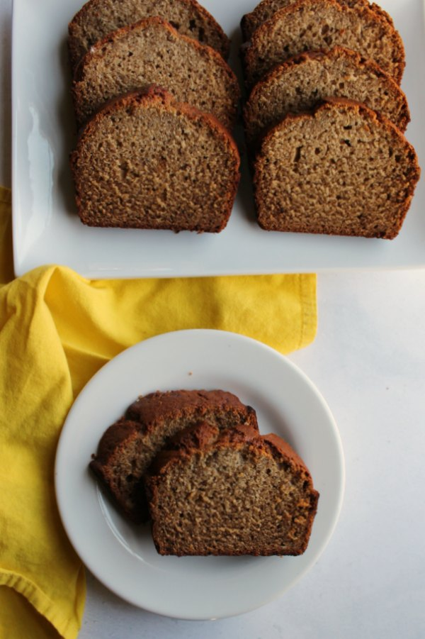 two slices of banana bread served on small plate with platter of slices in background