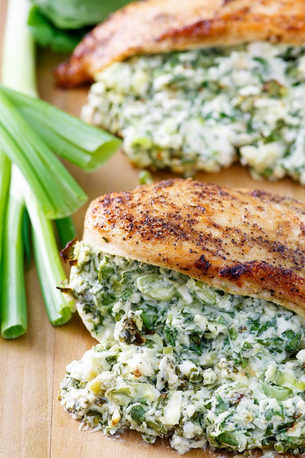close up of chicken breasts over stuffed with creamy spinach and feta cheese mixture with green onions nearby