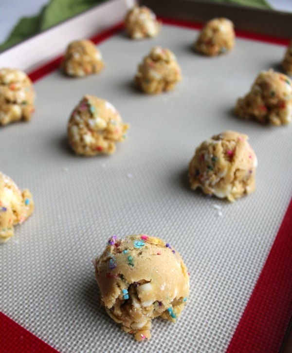 scoops of cookie dough on silicone mat lined baking sheet.