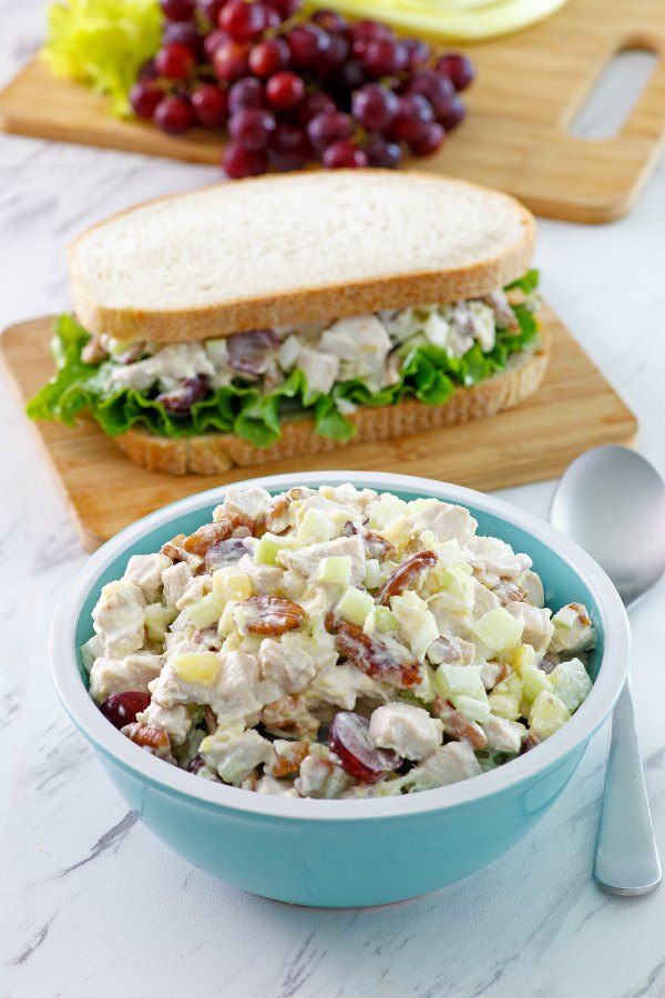 bowl of chicken salad with a sandwich nearby