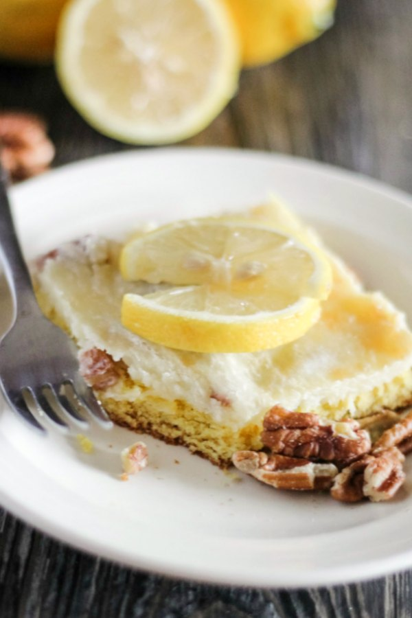 bite missing from square of lemon cake bars with pecans and cream cheese