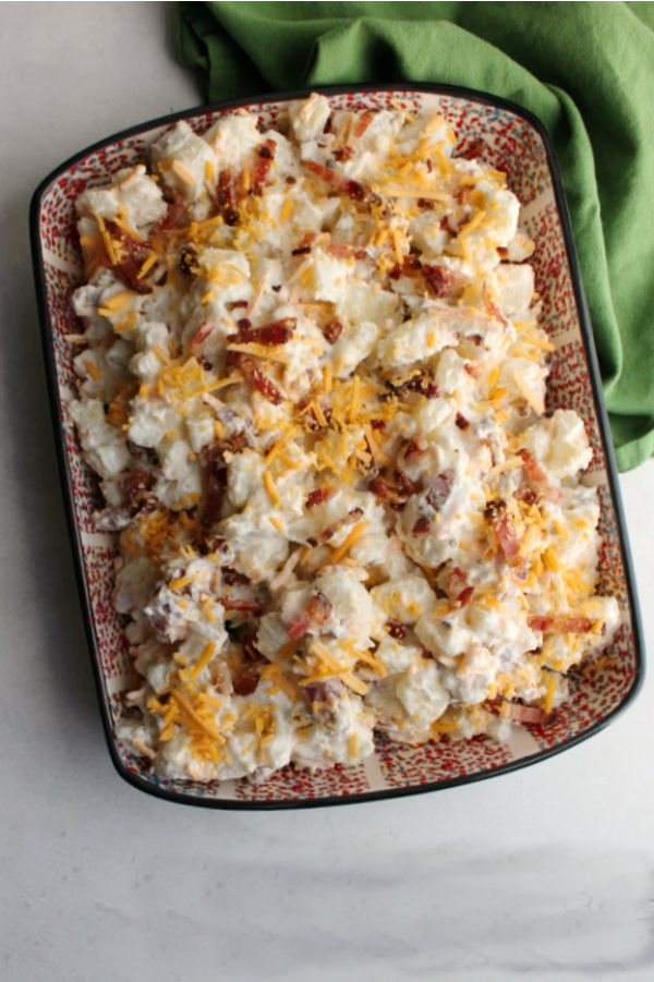 serving dish filled with cheddar bacon ranch potato salad ready to eat