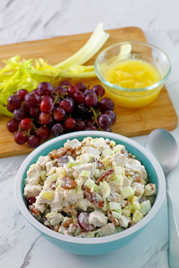 bowl of chicken salad with grapes, celery and pineapple in background
