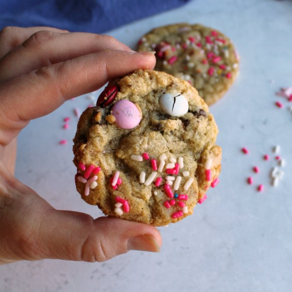 hand holding chewy cookie with pink and white m&ms and sprinkles