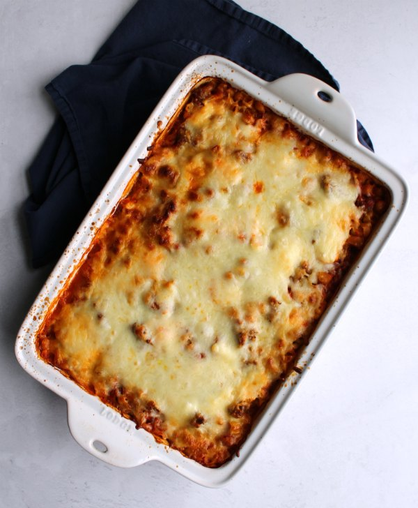 casserole dish filled with baked pasta topped with melted cheese, ready to serve.
