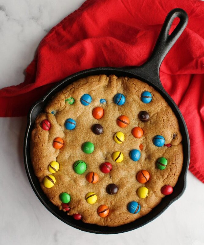 Cast iron skillet filled with peanut butter cookie topped with candy coated chocolates.