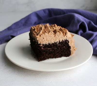 slice of chocolate sheet cake with fluffy chocolate buttercream on top