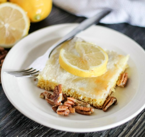 piece of lemon cake bar with cream cheese and pecan topping and lemon slices