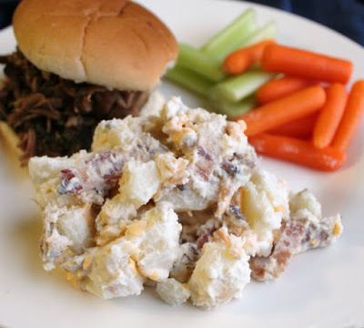 serving of potato salad on plate with pulled pork sandwich and veggies