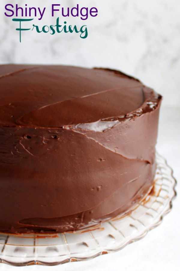 This glossy fudgy chocolate frosting is the perfect wrapper for a cake. It spreads so smoothly and it packs a big flavor punch.  You are going to love this vintage recipe for deliciously shiny fudge frosting!