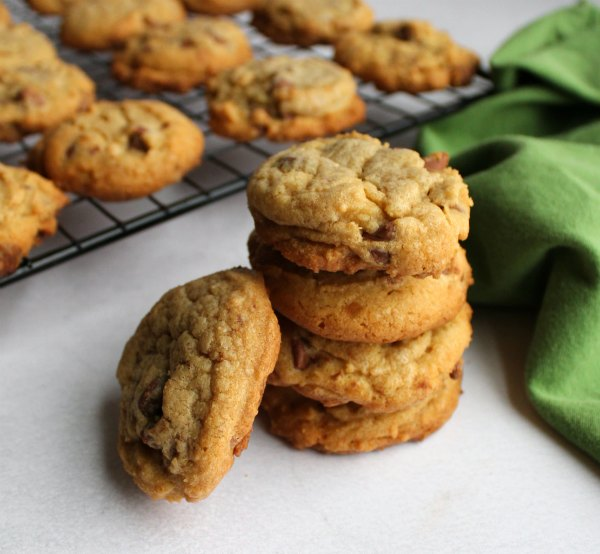 stack of soft chocolate chip cookies with more on cooling rack in the background