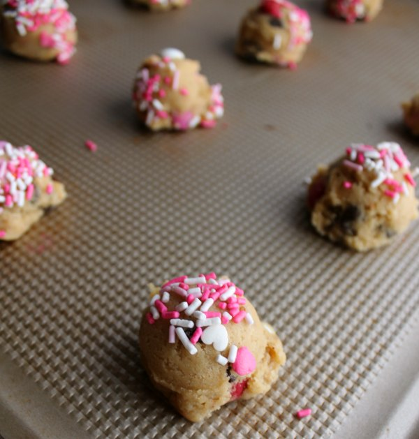 balls of cookie dough with some spinkles on top ready to bake.