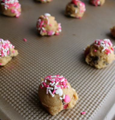 balls of cookie dough with some spinkles on top ready to bake
