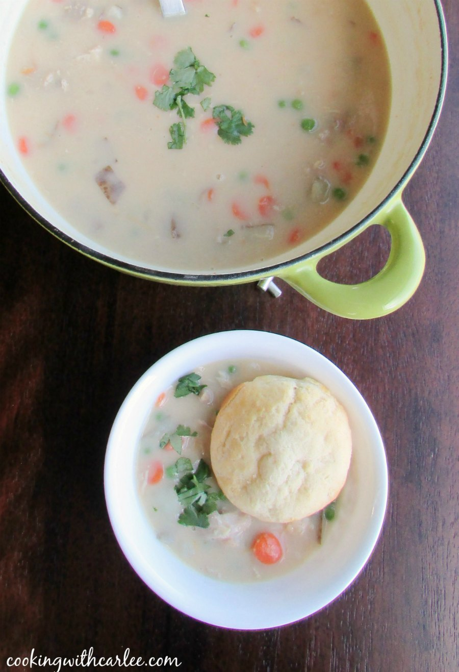 pot of creamy chicken pot pie soup with a bowl of soup served with a biscuit