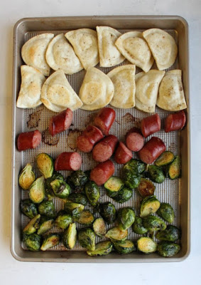 sheet pan filled with chunks of kielbasa, brussels sprouts and pierogi