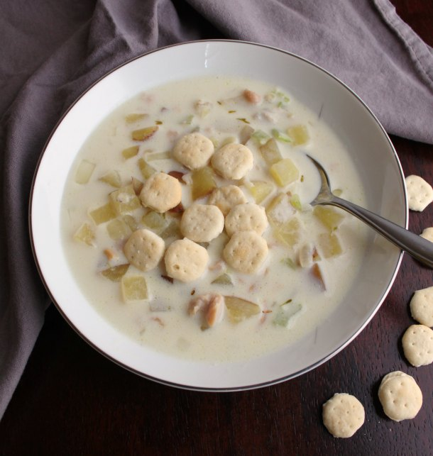 close up of spoon in bowl of creamy clam chowder with oyster crackers