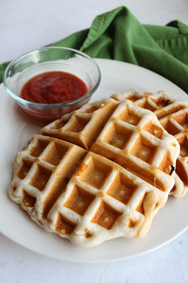 close up of plate with pizza waffles, one with a little hot cheese oozing out and a small cup of marinara