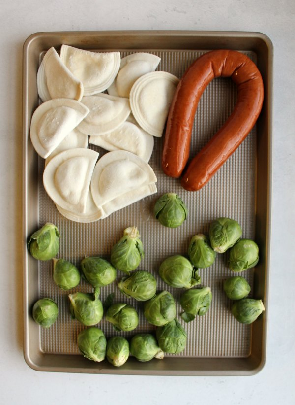 pierogi, whole brussels sprouts and whole sausage on sheet pan.