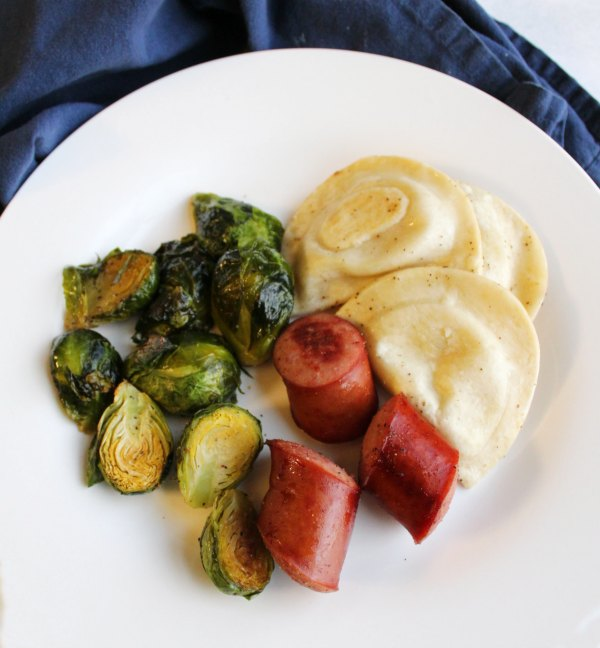 dinner plate of sheet pan meal with sausage, pierogies and brussels sprouts