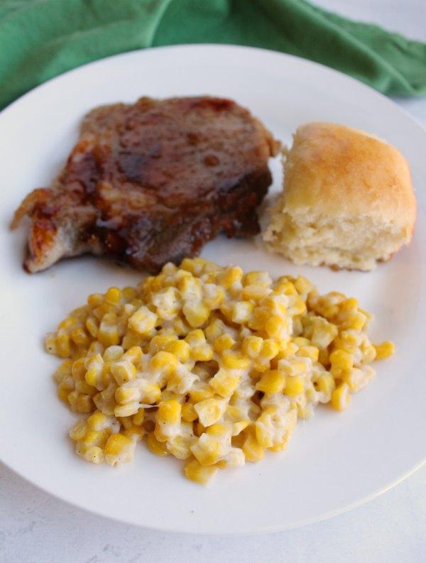 skillet corn with pork chop and hawaiian roll.