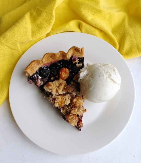 slice of blueberry and goldenberry pie with crumble topping and scoop of ice cream on plate.