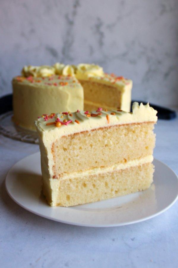 slice of lemon velvet cake served in front of remaining cake