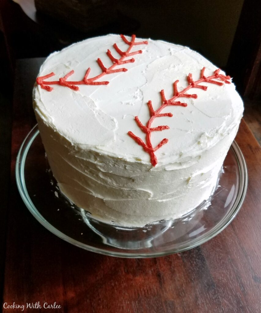 round layer cake iced with white chocolate buttercream and red laces to look like a baseball.