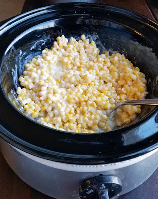 slow cooker full of creamy dairy coated corn ready to eat